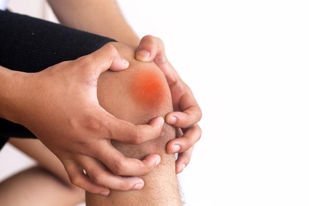 Bemannen sie das leiden unter den knieschmerzen und sich schlecht fühlen auf weißem hintergrund, gesundheitswesenkonzept