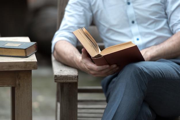 Bemannen sie das lesen eines buches auf einem stuhl im park, erfolgreiche leute, die morgens jeden tag lesen.