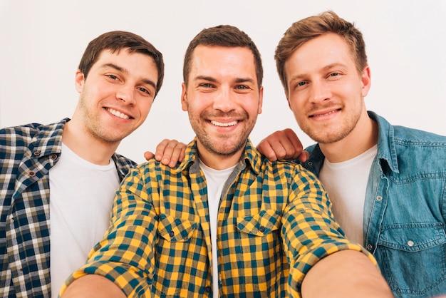 Bemannen sie das nehmen von selfie mit seinem freund gegen weißen hintergrund