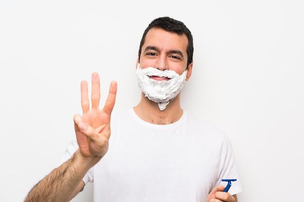 Bemannen sie das rasieren seines bartes über der lokalisierten weißen wand, die drei mit den fingern glücklich und gezählt worden sein würden