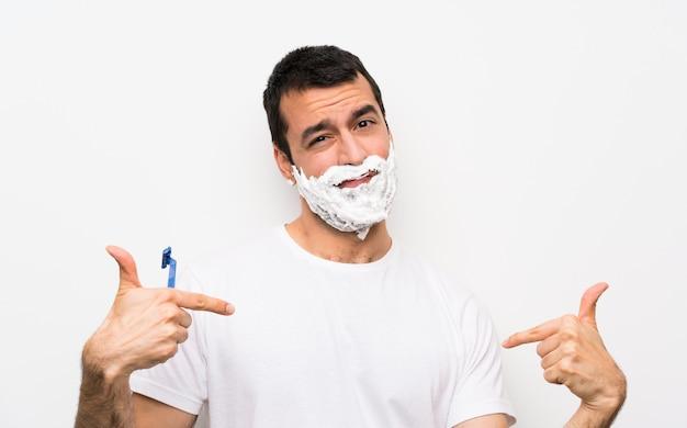 Bemannen sie das rasieren seines bartes über der lokalisierten weißen wand, die stolz und selbstzufrieden ist