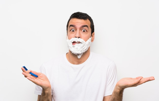 Bemannen sie das rasieren seines bartes über der lokalisierten weißen wand, die zweifel beim anheben der hände hat