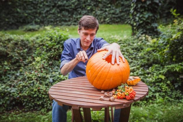 Bemannen sie das schnitzen des großen kürbises auf einem holztisch für halloween