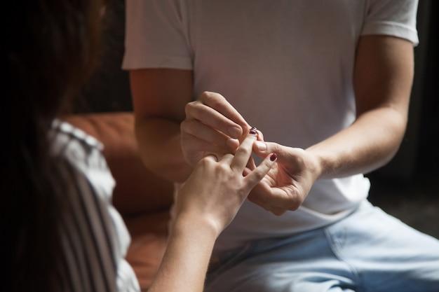 Bemannen sie das setzen des ringes auf den finger der frau, verpflichtungshochzeitskonzept, nahaufnahme