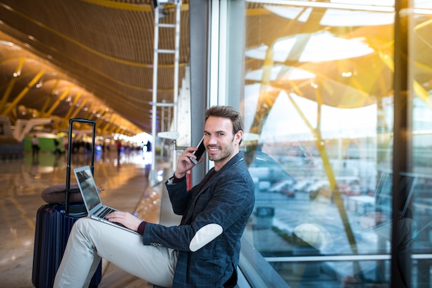 Bemannen sie das sitzen am flughafen unter verwendung des laptops und des handys nahe bei dem fenster