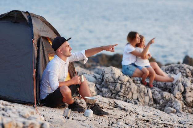 Bemannen sie das sitzen auf dem felsigen strand, der sonnenuntergang, frau und tochter betrachtet, die nahe sitzen.