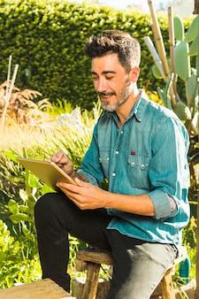Bemannen sie das sitzen im freien im park unter verwendung der digitalen tablette