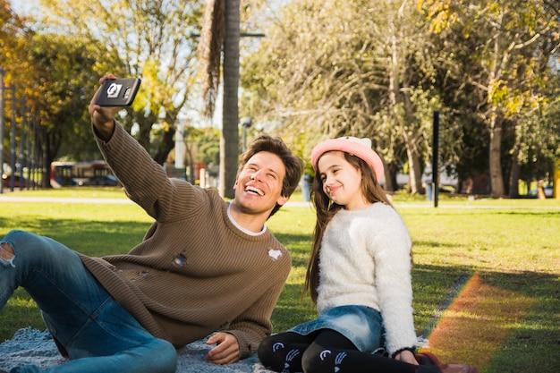Bemannen sie das sitzen im park mit seiner tochter, die selfie mit intelligentem telefon nimmt