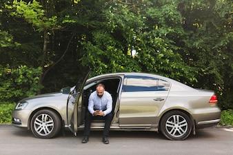 Bemannen Sie das Sitzen in einem Auto mit offener Tür unter Verwendung des Handys