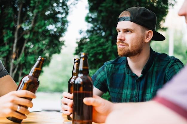 Bemannen sie das sitzen mit seinem freund, der braune bierflasche hält