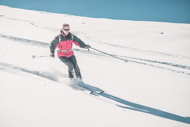 Bemannen sie das skifahren weg von der piste auf schneebedeckter steigung in den italienischen alpen