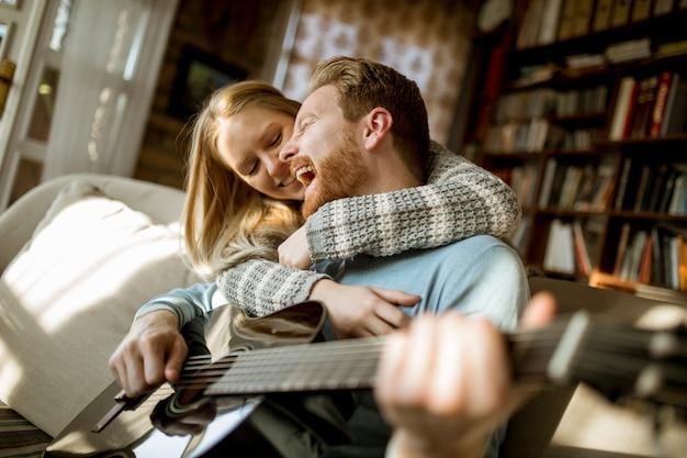 Bemannen sie das spielen der akustikgitarre auf dem sofa für seine junge schöne frau