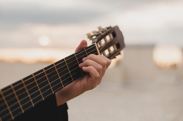 Bemannen sie das spielen der gitarre auf der dachspitze auf dem hintergrund des sonnenuntergangs