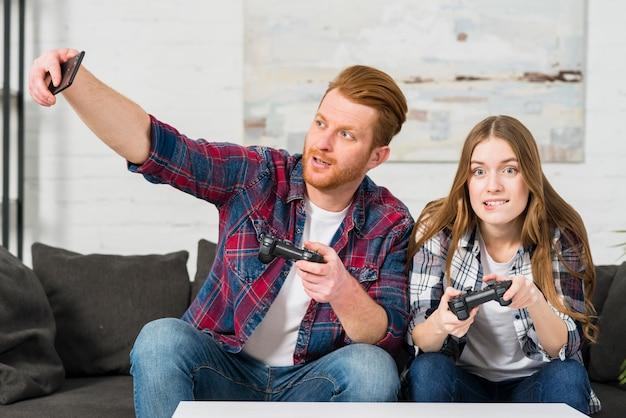Bemannen sie das spielen des videospiels mit ihrer freundin, die selfie auf smartphone nimmt
