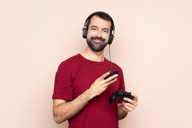 Bemannen sie das spielen mit einem videospielprüfer über der lokalisierten wand, die eine mitteilung mit dem mobile sendet