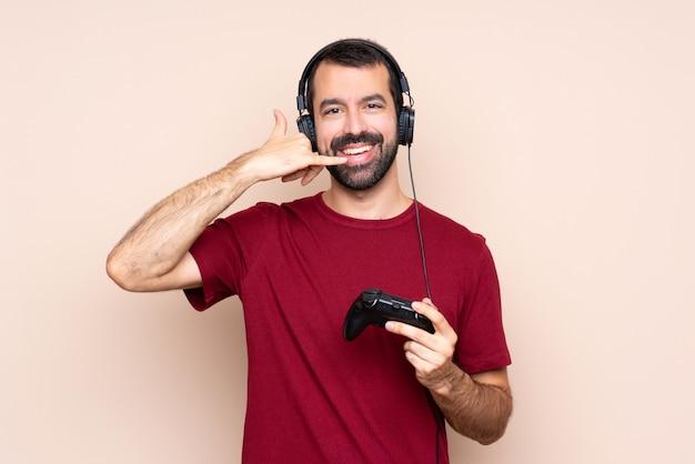 Bemannen sie das spielen mit einem videospielprüfer über der lokalisierten wand, die telefongeste macht. rufen sie mich zurück zu unterzeichnen