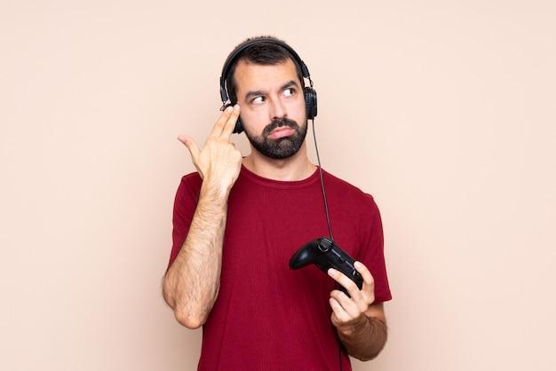 Bemannen sie das spielen mit einem videospielprüfer über lokalisierter wand mit den problemen, die selbstmordgeste machen