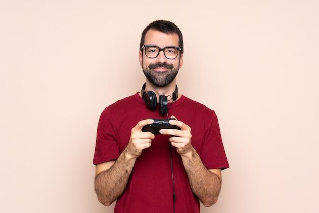 Bemannen sie das spielen mit einem videospielprüfer über lokalisierter wand mit gläsern und glücklich