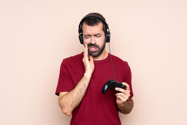 Bemannen sie das spielen mit einem videospielprüfer über lokalisierter wand mit zahnschmerzen