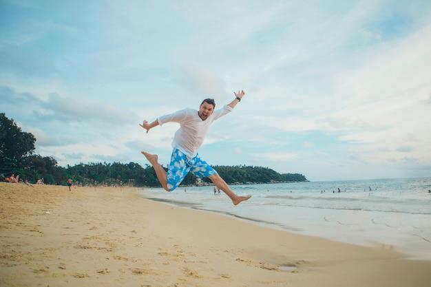Bemannen sie das springen glücklich in den strand mit einem blauen himmel und einem meer