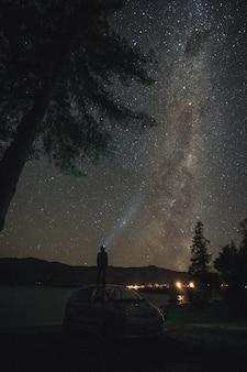 Bemannen sie das stellung auf dem auto, das milchstraßegalaxie betrachtet