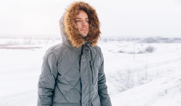 Bemannen sie das tragen der grauen winterjacke mit haube an im winterschnee