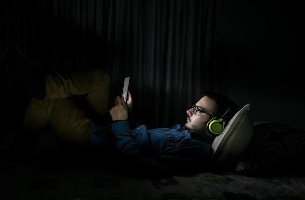 Bemannen sie das überwachen von fernsehserien in einer tablette, die zu hause auf einem bett in der nacht sitzt