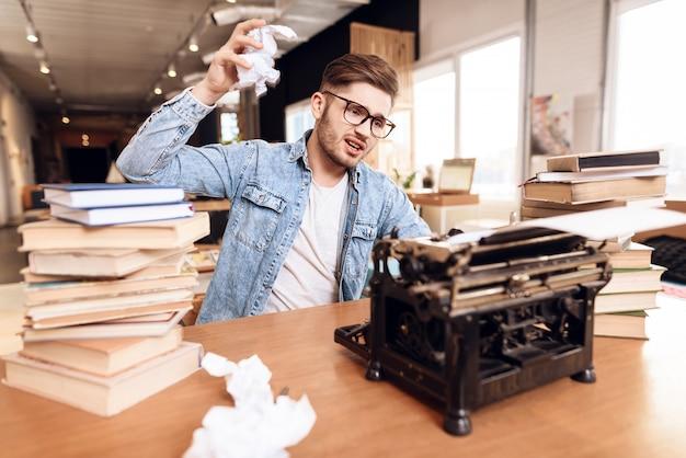 Bemannen sie das verkratzen von anmerkungen an der alten schreibmaschine, die am schreibtisch sitzt.