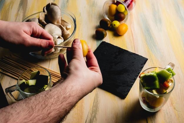 Bemannen sie das vorbereiten von aufsteckspindeln des gemüses auf einem alten holztisch. vegane, vegetarische ernährung.
