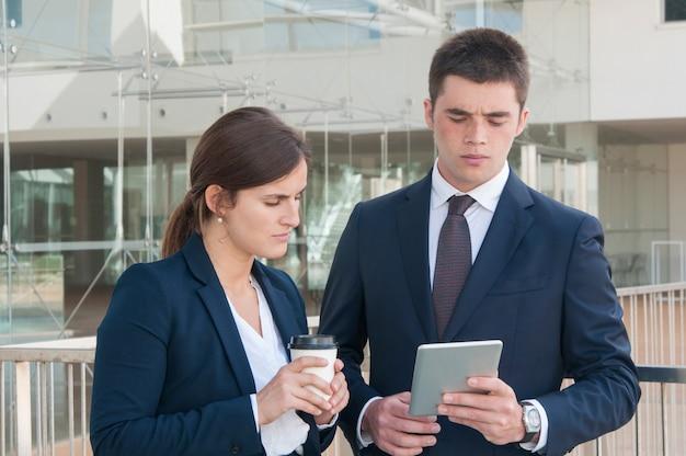 Bemannen sie das zeigen von daten bezüglich der tablette, die schauende frau und kaffee halten