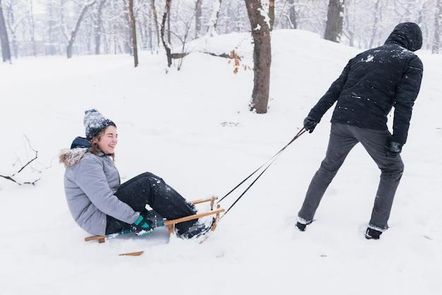 Bemannen sie das ziehen des lächelnden mädchens auf schlitten durch schneebedeckte landschaft