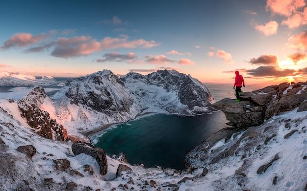 Bemannen sie den bergsteiger, der auf felsen des höchstberges bei sonnenuntergang steht