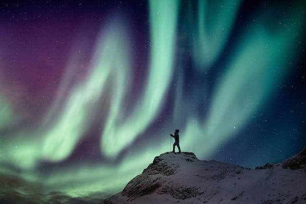 Bemannen sie den bergsteiger, der auf schneebedeckter spitze mit aurora borealis und sternenklarem hintergrund steht