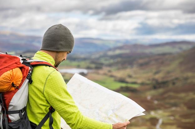 Bemannen sie den forscher, der eine karte oben auf bergwanderweg schaut