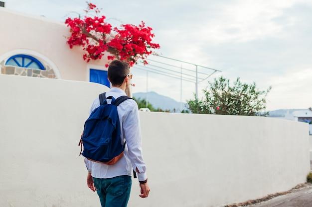 Bemannen sie den reisenden, der in akrotiri-dorf auf santorini-insel, griechenland geht. touristische bewundernde architekturlandschaft