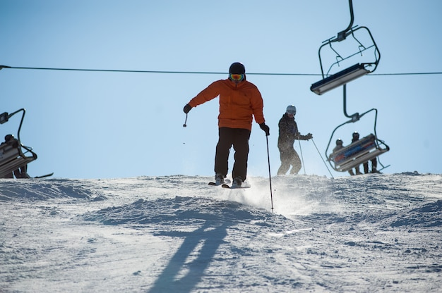 Bemannen sie den skifahrer, der abwärts am skiort gegen skilift ski fährt