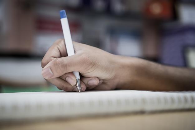 Bemannen sie den studenten, der kenntnisse über notizbuch mit stift in bibliothek an der collegeuniversität für hausarbeit nimmt und schreibt