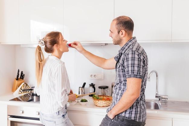 Bemannen sie die fütterung des frischen gesunden roten rettichs zu seiner freundin in der küche