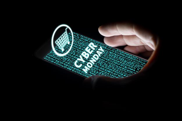 Bemannen sie die hände, die intelligentes telefon mit cybermontag-text und warenkorb auf virtuellen schirmen auf smartphone halten.
