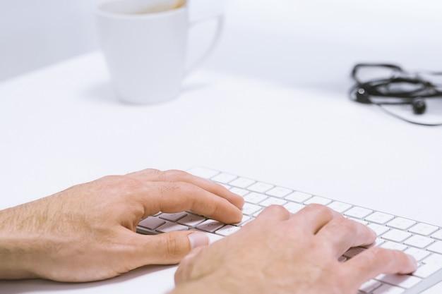 Bemannen sie die hand, die das arbeiten an drahtloser tastatur auf weißem arbeitsplatz schreibt