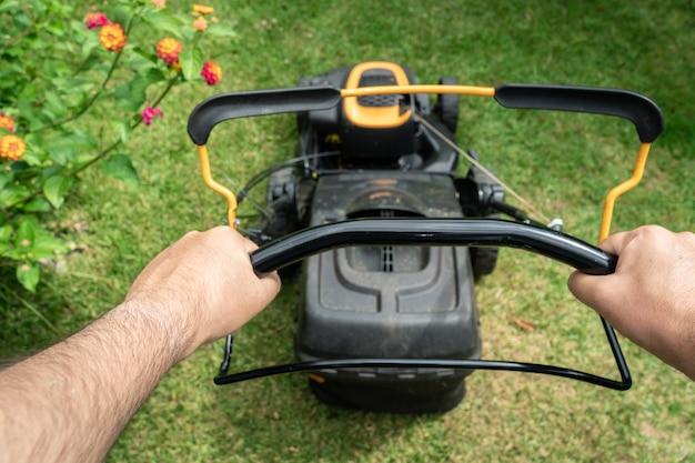 Bemannen sie die hand, die eine rasenmähermaschine zum schneiden des grünen grases hält