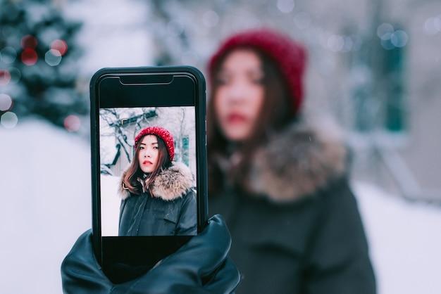 Bemannen sie die hand, die foto der frau mit smartphonekamera macht