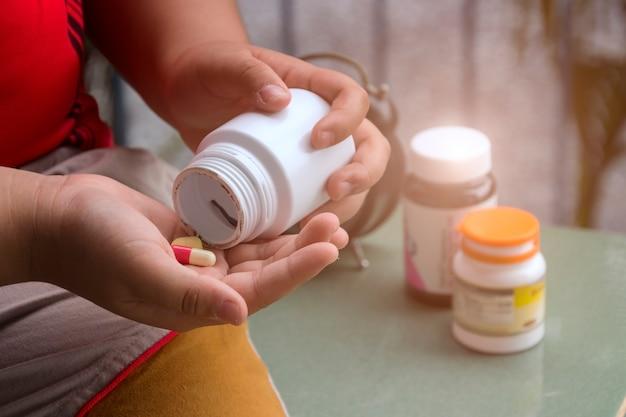 Bemannen sie die hand, die frug medizinflasche auf der kräuterergänzungspille hält und gesund essen