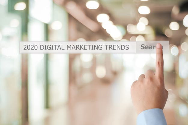 Bemannen sie die hand, die geschäftsstrategie der digitalen marketing-tendenz 2020 auf suchstange über unschärfebüro berührt