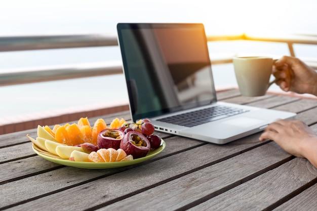 Bemannen sie die hand, die kaffee und die frische frucht arbeitet an laptop hält