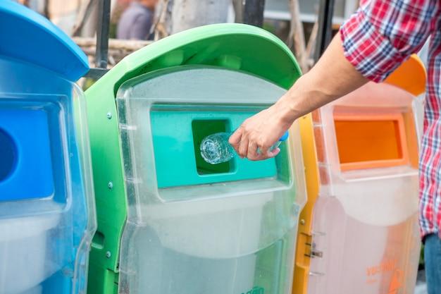 Bemannen sie die hand, die plastikflaschenabfall in abfallabfall hält und setzt.