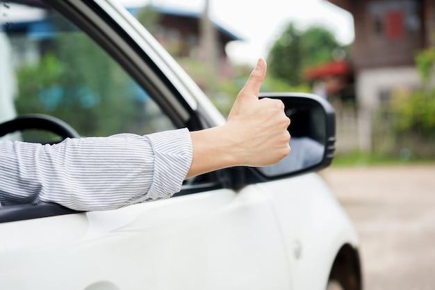 Bemannen sie die hand, die sich daumen durch das fenster des autos zur sicherheit des fahrens des konzeptes zeigt.