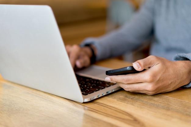 Bemannen sie die hand, die smartphone hält und schreibt, arbeitend an laptop