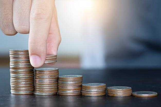 Bemannen sie die hand, welche die münzen setzt, die für wachstumsgeschäft stapeln und investition sparen