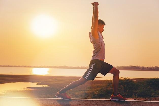 Bemannen sie die läuferathleten, die oben für übung im freien mit sonnenunterganghintergrund entwurmieren